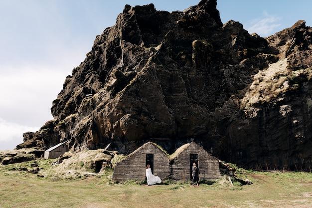 Casal de noivos posando em casas antigas cobertas de musgo no fundo de uma montanha rochosa