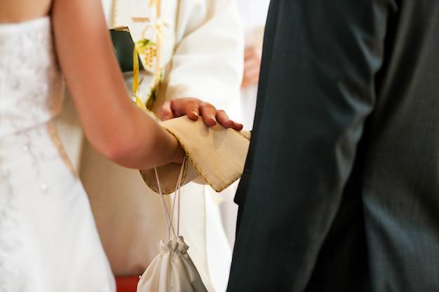 Casal de noivos recebendo bênção do padre