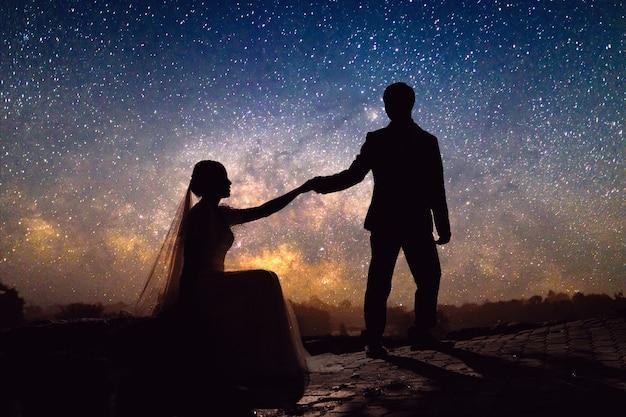 Casal de noivos românticos de silhueta segurando a mão na colina de grama na via láctea com campo de estrelas