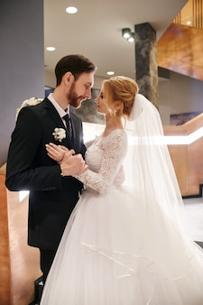Casal de noivos se abraçando e beijando, o primeiro dia de vida juntos. noiva e noivo após a cerimônia de casamento, lindo casal se ama e se abraça