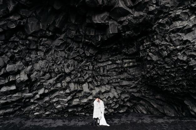Casal de noivos sob uma rocha de pedras de basalto a noiva e o noivo em uma praia negra de vik protegida por um