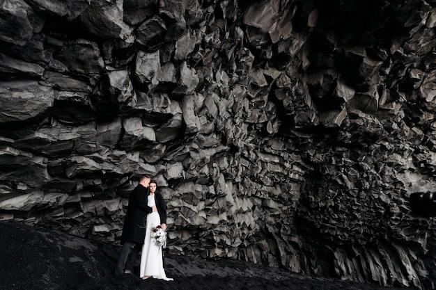 Casal de noivos sob uma rocha de pedras de basalto