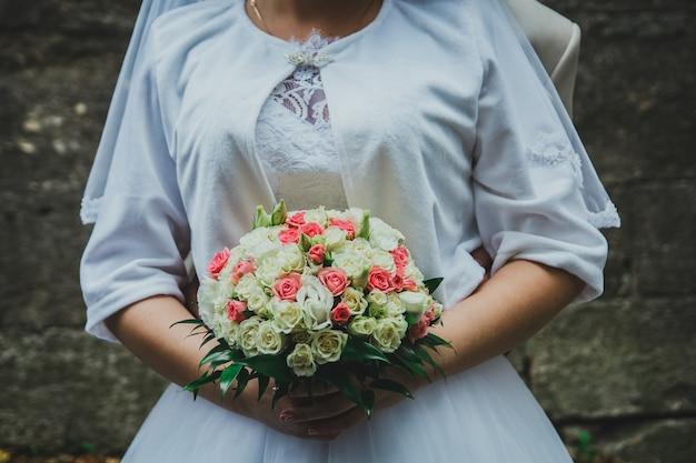 Casal de noivos tem buquê de rosas rosa e bege quentes nas mãos.