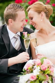 Casal de noivos tilintar de copos de champanhe
