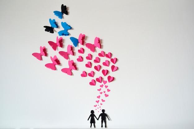 Casal de papel romântico com corações e borboletas voando