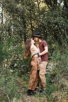 Casal de pedestrianismo apaixonado beijando na natureza