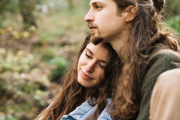 Casal de pedestrianismo apaixonado sentado na natureza
