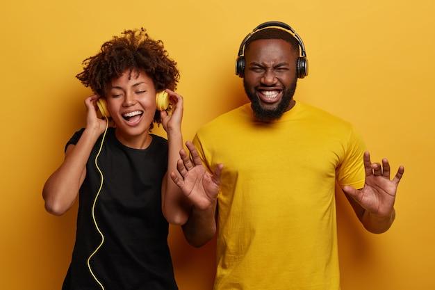 Casal de pele escura, enérgico e animado, dançam e se divertem juntos, ouvem diferentes tipos de música em fones de ouvido isolados no fundo brilhante.