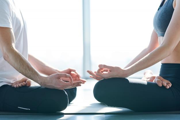 Casal de pernas cruzadas sentado no tapete em pose de lótus, um na frente do outro, enquanto relaxa após o treinamento de ioga