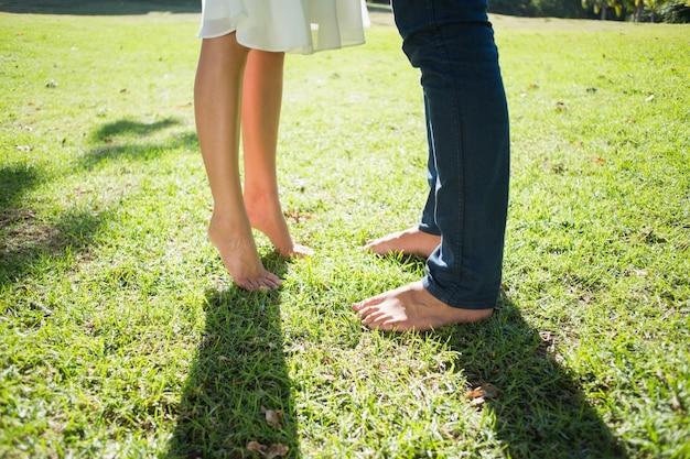 Casal de pés descalços de pé na grama