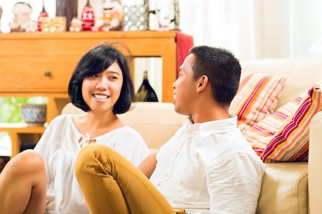 Casal de pessoas asiáticas na sala de estar