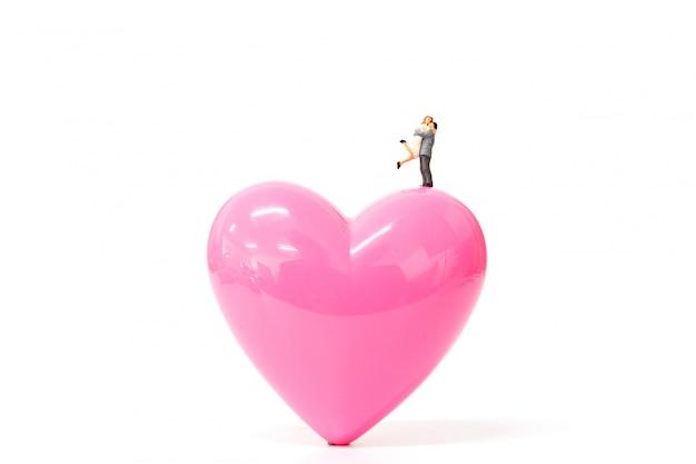 Casal de pessoas em miniatura com coração rosa em fundo branco