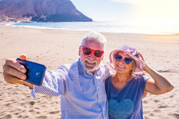 Casal de pessoas maduras ou aposentados curtindo as férias e o verão juntos na areia