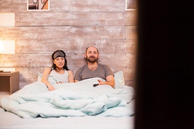 Casal de pijama sentado lado a lado enquanto assiste tv.