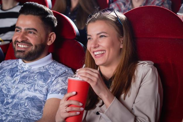 Casal de positividade de loira em homem cinza e árabe em camisa azul, bebendo e sorrindo, passando o tempo no cinema. alunos se divertindo, ao olhar para a tela da sala de cinema moderna.