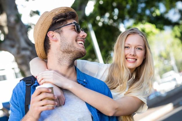 Casal de quadril abraçando e sorrindo na rua