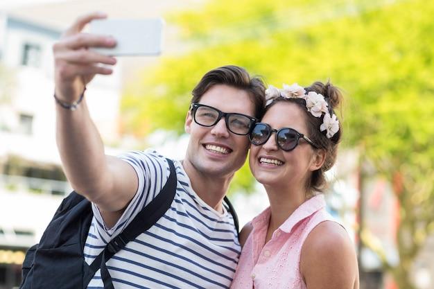 Casal de quadril tomando selfie na rua