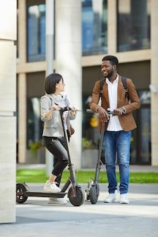 Casal de raça mista andando de scooter elétrico