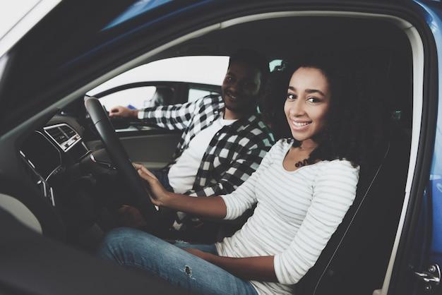 Casal de raça mista feliz no carro de teste de lugares de carro