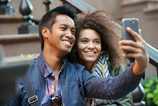Casal de raça mista tirando foto de selfie