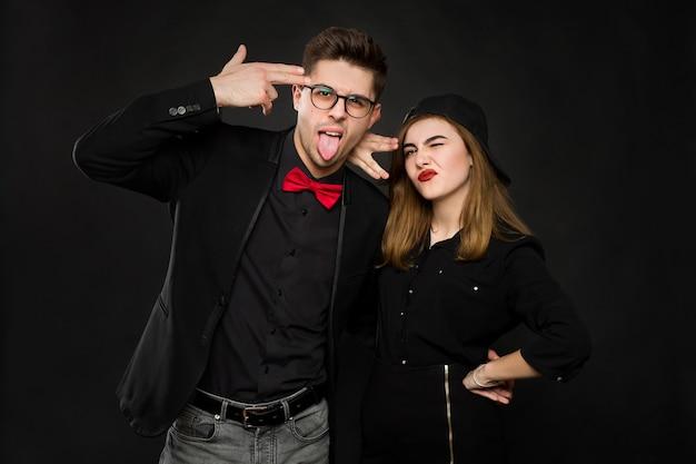 Casal de rap sorridente adolescente em roupas pretas e um boné preto mostram sinais com as mãos e a língua. cores isoladas em um fundo preto.