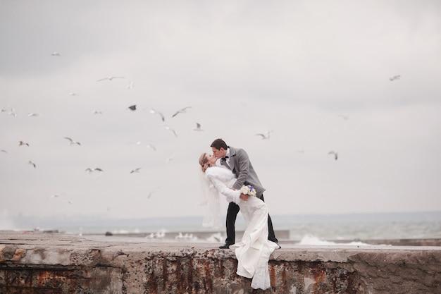 Casal de recém-casados se beijando no mar