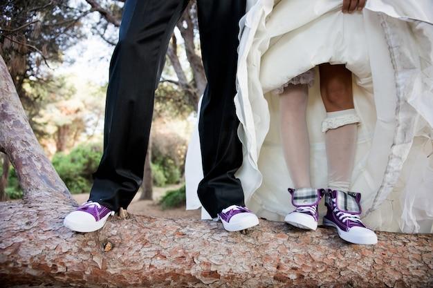 Casal de recém casamentos com tênis iguais engraçados.