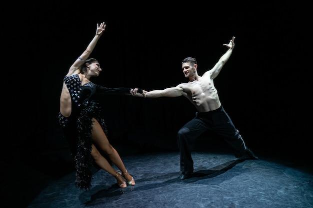 Casal de salão de baile dançando isolado no preto.