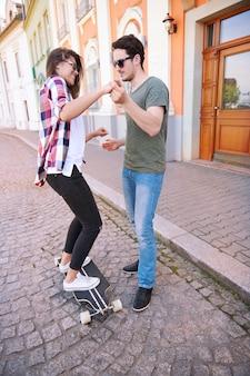 Casal de skatistas treinando na rua
