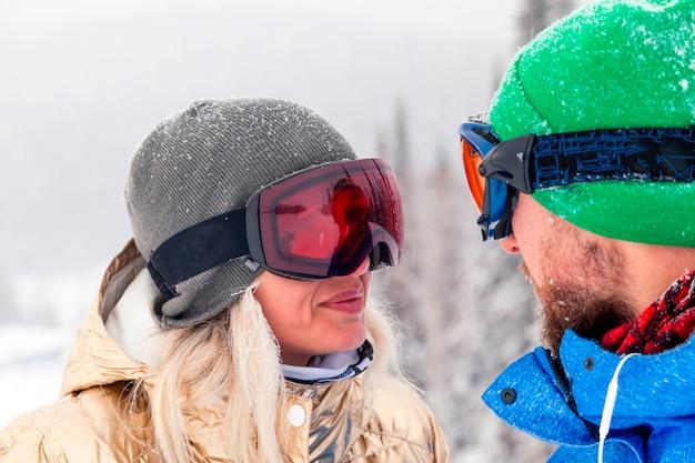 Casal de snowboard no sportswear brilhante e roupa nas montanhas altas ensolaradas e nevadas. borrão, foco suave, objeto em movimento. lua de mel conceito, descanso ao ar livre