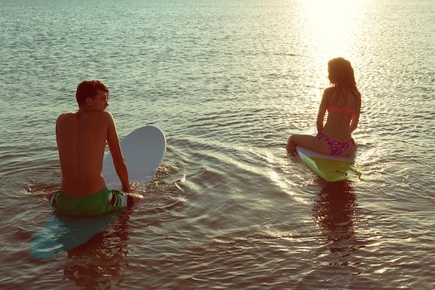 Casal de surf apoiando-se em pranchas de surf no mar