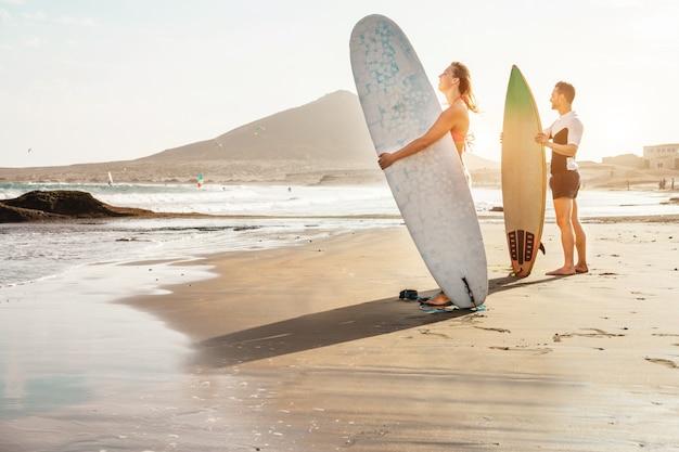 Casal de surfistas esperando as ondas altas na praia - pessoas desportivas com pranchas de surf ao pôr do sol - esporte radical e conceito de férias - foco no rosto feminino