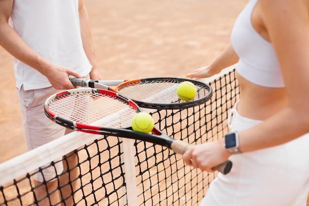 Casal de tênis de alto ângulo com raquetes
