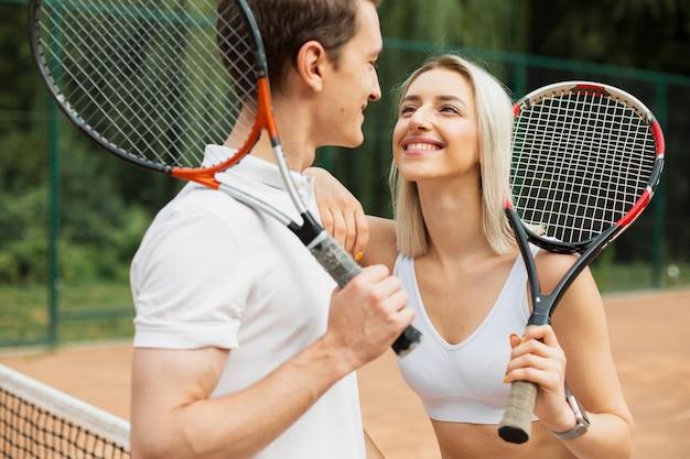 Casal de tênis sorrindo um ao outro