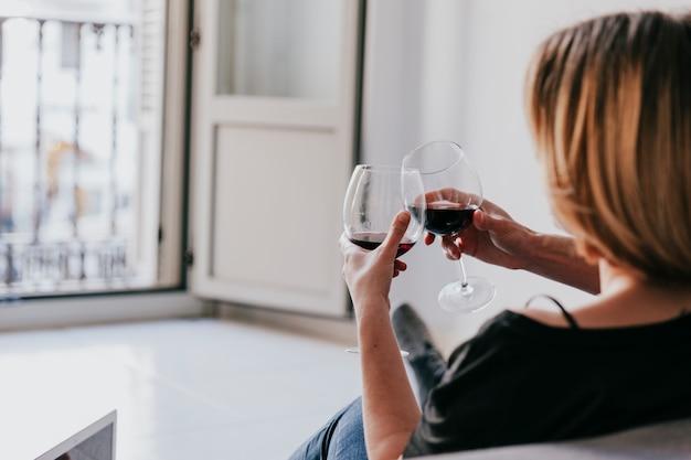 Casal de tilintar vinho no sofá