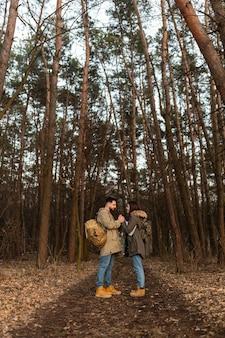 Casal de tiro certeiro de mãos dadas na floresta