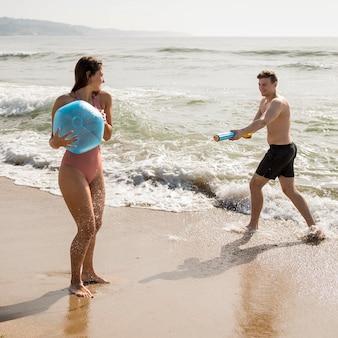 Casal de tiro completo brincando na praia