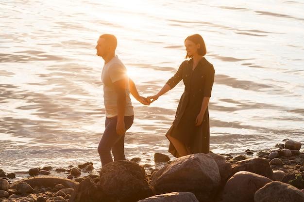 Casal de tiro completo caminhando na costa