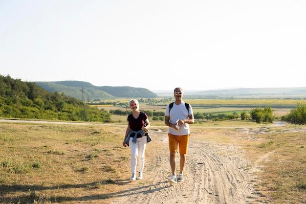Casal de tiro completo caminhando na estrada