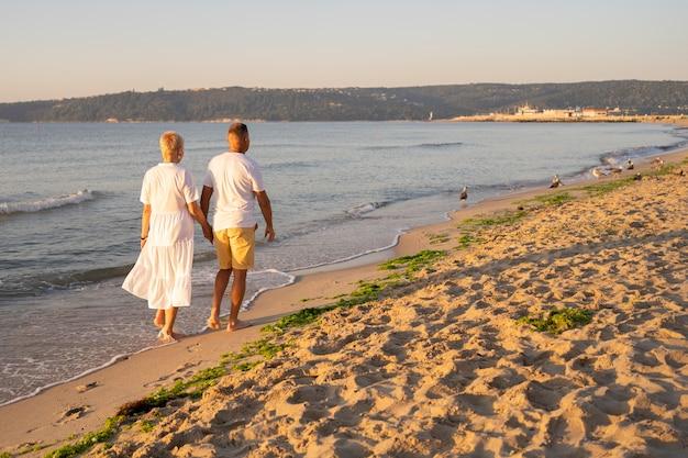 Casal de tiro completo caminhando na praia