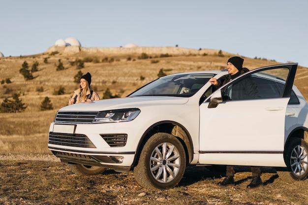 Casal de tiro completo com carro na natureza