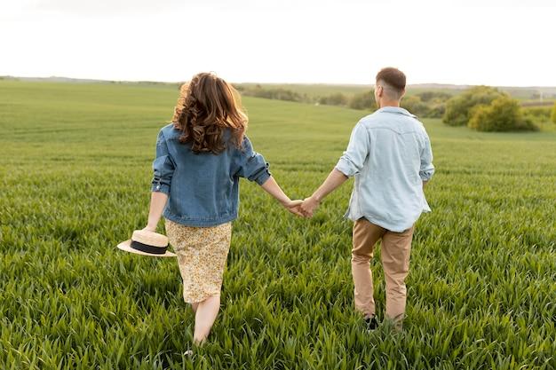 Casal de tiro completo de mãos dadas na natureza