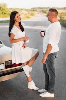 Casal de tiro completo falando perto do carro