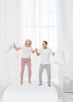 Casal de tiro completo pulando na cama