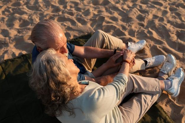 Casal de tiro completo sentado na praia