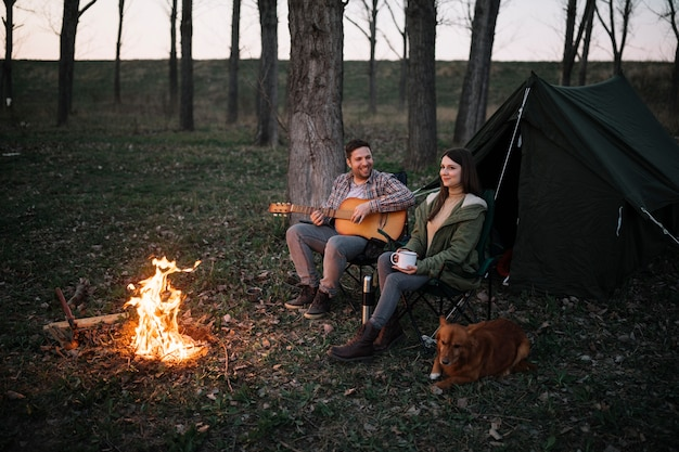 Casal de tiro completo tocando violão