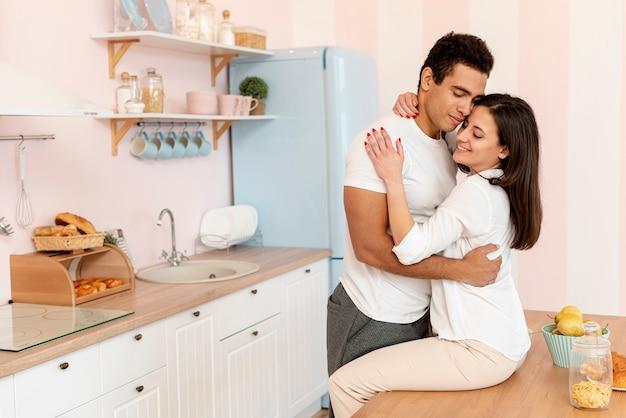 Casal de tiro médio abraçando na cozinha
