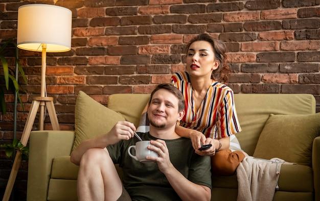 Casal de tiro médio assistindo tv