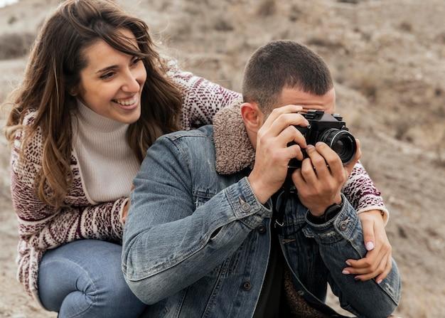 Casal de tiro médio com câmera fotográfica