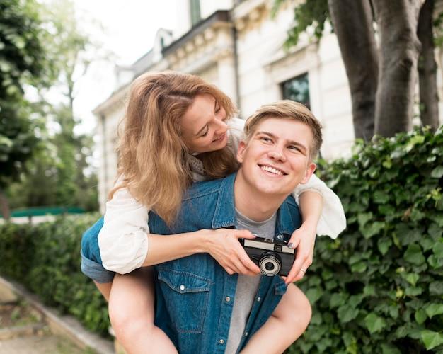 Casal de tiro médio com câmera posando
